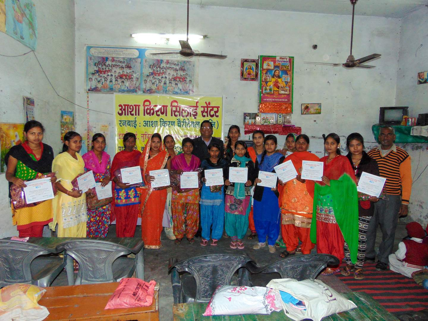 A group of women display their certificates after completing their sewing course and learning to manage money.